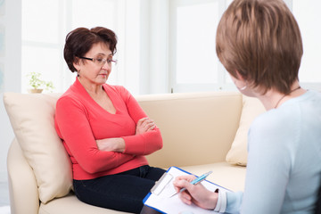 An elderly woman talking to psychologist