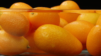 Kumquat in a transparent bowl close up.