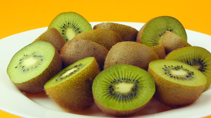 Halves an kiwi fruits on a white plate.