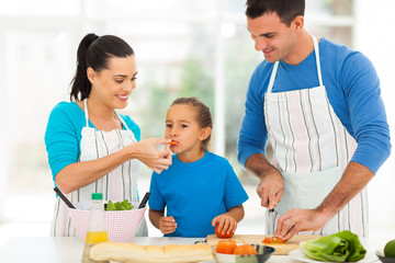 little girl tasting tomato while parents cooking