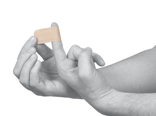Hand putting Adhesive Bandage on man finger.