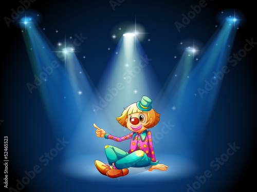 A stage with a female clown sitting at the center
