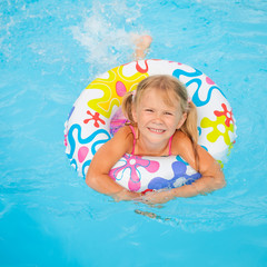 little girl in the swimming pool  with rubber ring
