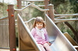 baby girl on slide at playground