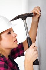Junge Heimwerkerin klopft konzentriert Nagel in Wand