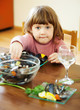 child eats mussels in home