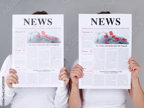 Two girls reading newspaper