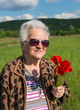 Elderly woman in sunglasses with bunch of poppies