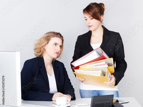 Two female office assistants have to much work