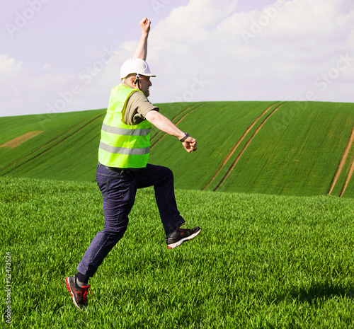Engeeneer jumping for joy on green field