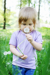 girl smelling dandelion