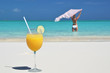 Glass of orange juice on the sandy beach of Exuma, Bahamas