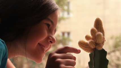 Girl touches a cactus. Experience acquisition.