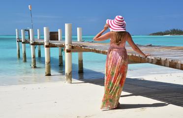 Girl at the wooden jetty looking to the ocean. Exuma, Bahamas