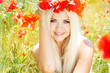 Young girl with long blonde hair in poppies field