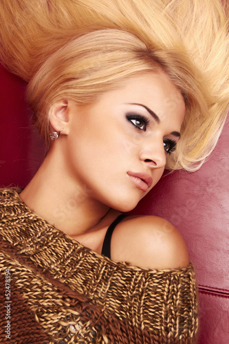 beautiful blond woman laying on a red leather sofa