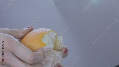 Hands of young woman peel orange with splashes.