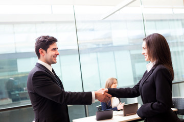 Business people shaking hands, finishing up a meeting at the off