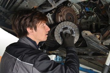 Auto mechanic working under the car and changing clutch