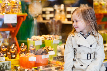 Little girl looking at chocolate in shop
