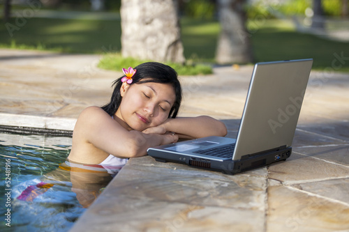 Enjoying holiday with laptop in the pool