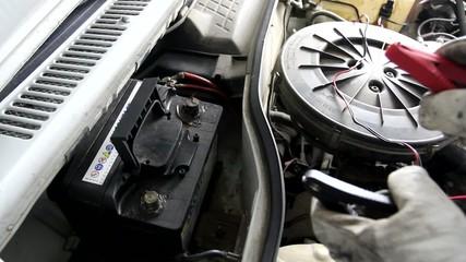 Mecanico poniendo pinzas a la bateria de un coche