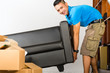 Young asian man lifting a couch