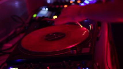 DJ scratching vinyl record plate in nightclub