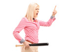 Violent young woman holding a baseball bat and threatening