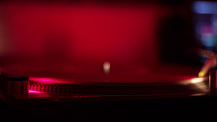 DJ hand places stylus on a turntable vinyl record in nightclub