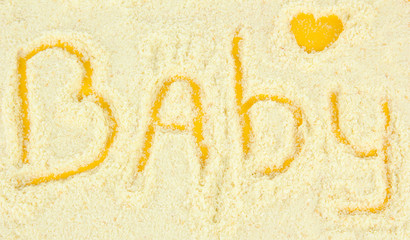 Word baby making with powdered milk on yellow background