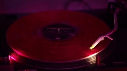 Turntable spinning vinyl record in nightclub.