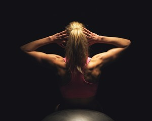 Woman Lying on Fitness Ball and Doing Sit Ups