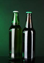 Bottles of beer on green background