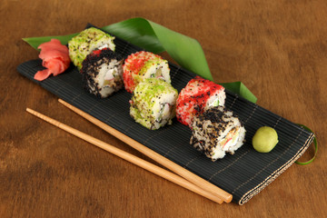 Tasty Maki sushi - Roll on mat on brown background
