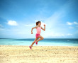 Little girl running along the ocean