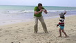 Father taking picture of his son on the beach, super slow motion