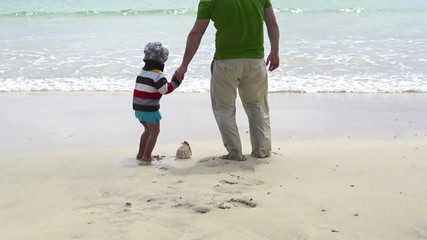 Father and son find beautiful seashell on the beach