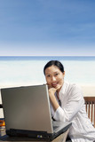Asian entrepreneur working with laptop at beach