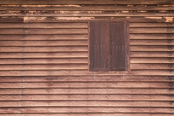 Wooden wall of ancient house with window closed