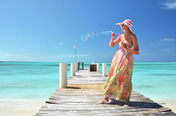 Girl on the wooden jetty making soap bubbles. Exuma, Bahamas
