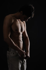 Muscular Man looking his body isolated black background