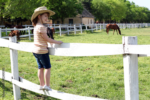 little girl with cowboy hat standing on corral and watching hors