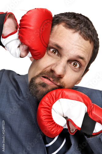 Close-up young businessman struck by hands in boxing gloves Poster