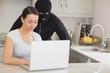 Woman using laptop while burgler is watching