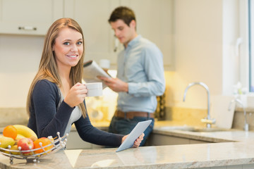 Woman drinking hot beverage using tablet pc in kitchen