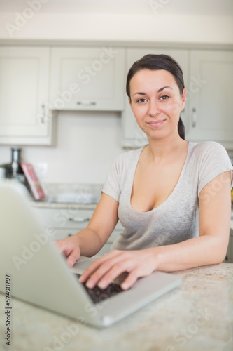 Woman typing on laptop in the kitchen