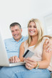 Husband and wife shopping online with laptop