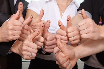 Viele Daumen mit Smileys im Büro
