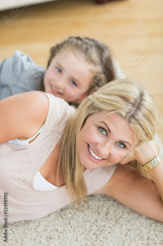 Mother and daughter resting on floor